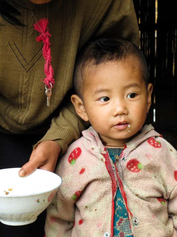 Carnets de voyage en Birmanie 2010. A proximité de la ville de Kalaw, dans l'état Shan, une mère portant les clés de sa maison à son cou dans un village de montagne donne à manger à son enfant sur la route du lac Inle.Photo Mathieu THOMASSET